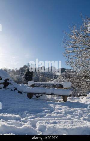 Winter snow covered wooden bench on canal in Kinver, Staffordshire with trees and church in the background - Stock Photo