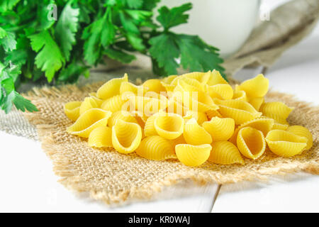 Culinary background with conchiglie pasta on wooden table. Pasta in the form of seashells on a sack with parsley - Stock Photo
