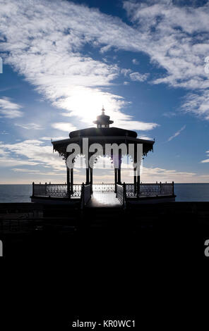 Brighton victorian bandstand silhoutted black by sun behind it, dramatic blue and white cloudy sky, black forground, - Stock Photo