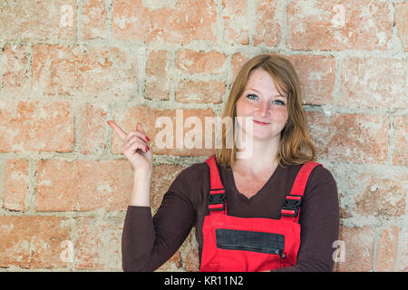 Smiling redhead young woman dressed in red overall is standing  in front of an old brick wall. Woman is looking - Stock Photo
