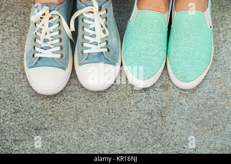 Close up view of two pairs teen's feet feet in blue sneakers