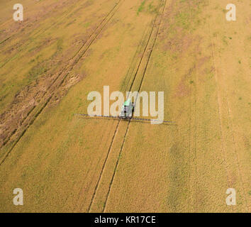 Adding herbicide tractor on the field of ripe wheat. View from above. - Stock Photo