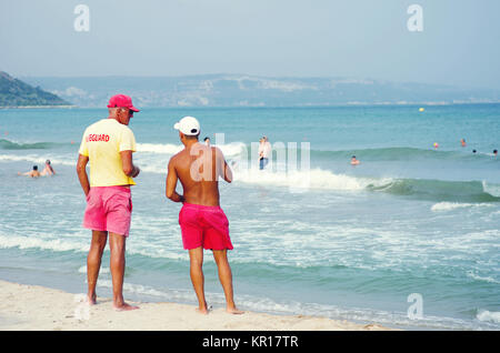 Two men lifeguards standing at the shoreline and talking. - Stock Photo