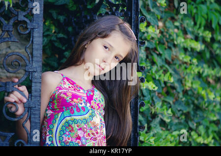 Beautiful young girl peering behind wrought iron door in the Botanical garden in Balchik, Bulgaria. - Stock Photo