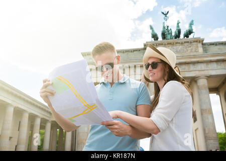 Young Couple Looking At Map - Stock Photo