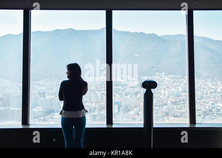 Rear view of a girl looking at city view from an observation tower, Daegu, South Korea - Stock Photo