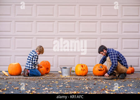 Father And Son Sitting By A Garage Door Carving Halloween Pumpkins   Stock  Photo