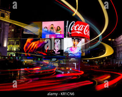 wild lights on the ever crowded Piccadilly Circus with car lights and advertising hoardings illuminating the night - Stock Photo