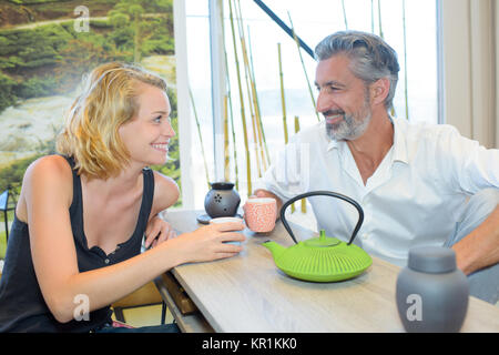 Man and lady enjoying a hot drink together - Stock Photo