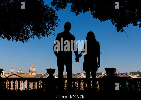 Silhouette couple holding hands overlooking the city of Rome Italy - Stock Photo