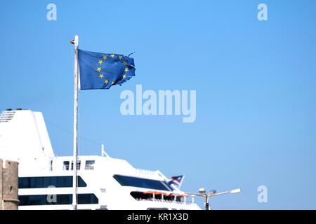A ragged, torn, sorry looking and battered flag of the European Union flying in a strong wind on the island of Rhodes, - Stock Photo