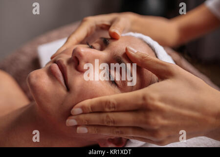 Close up of a woman having facial beauty treatment at spa salon. Beautiful young woman getting a face massage. - Stock Photo