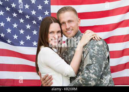 Male Soldier With His Wife In Front Of American Flag - Stock Photo