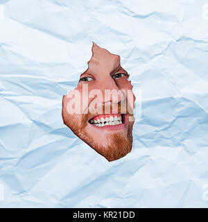 Young man looking through paper rip - Stock Photo