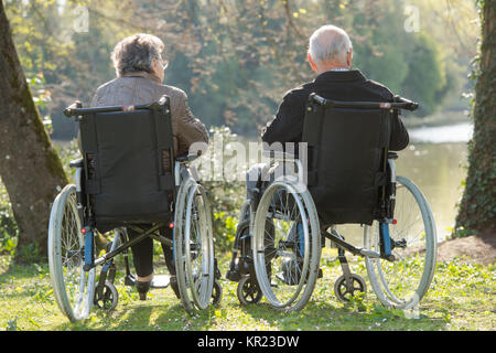 Elderly couple in wheelchairs, looking at view - Stock Photo
