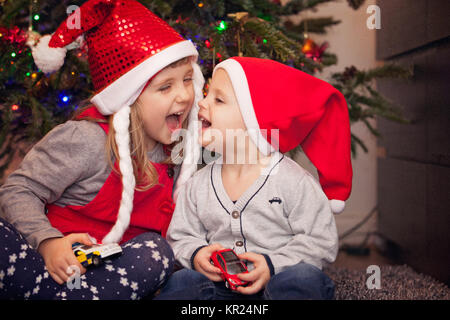 Brother and sister under Christmas tree - Stock Photo
