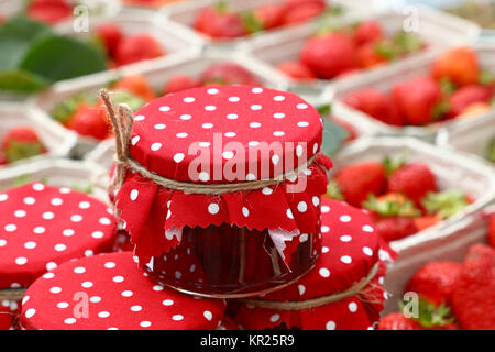 Close up of small glass jars of berry jam with red dotted rustic top lid textile decoration and twine bow over background - Stock Photo