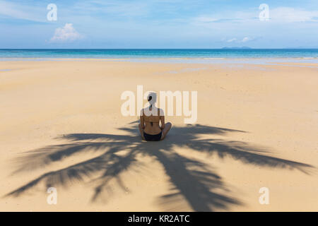 Young woman sitting in the shadow of palm tree on tropical beach on Koh Kood island, Thailand - Stock Photo