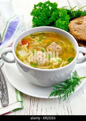 Soup with meatballs and noodles in white bowl on board - Stock Photo
