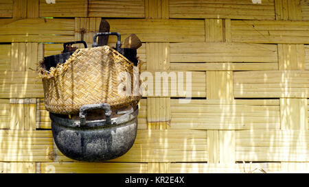 Local stove kitchen outdoor on woven bamboo strips wall - Stock Photo