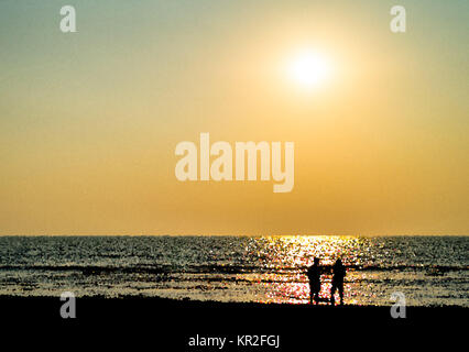 Two freinds silhouette meeting ocean sunset landscape backdrop - Stock Photo