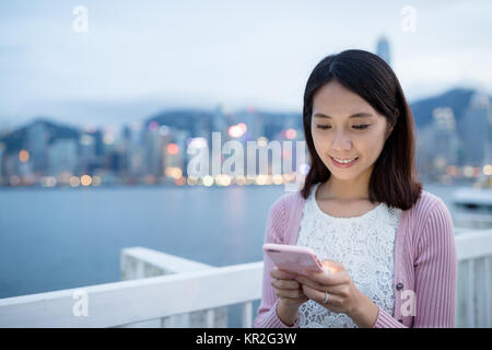 Young woman use of smart phone at night - Stock Photo