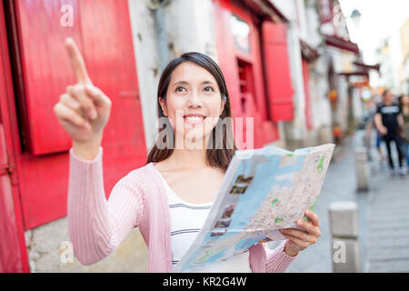 Woman finding destination on city map - Stock Photo
