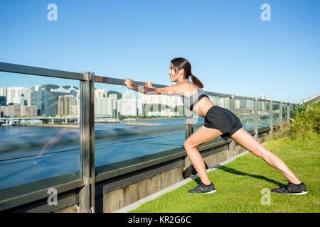 Woman doing warm up exercise at outdoor - Stock Photo