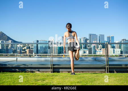 The back view of woman doing warm up exercise at city - Stock Photo