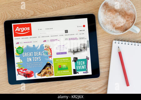 The Argos website on an iPad tablet device which rests on a wooden table beside a notepad and pencil and a cup of - Stock Photo