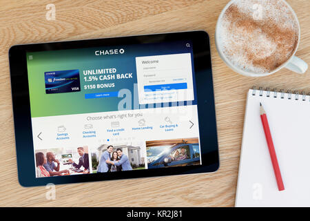 The Chase website on an iPad tablet device which rests on a wooden table beside a notepad and pencil and a cup of - Stock Photo