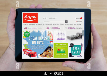 A man looks at the Argos website on his iPad tablet device, shot against a wooden table top background (Editorial - Stock Photo