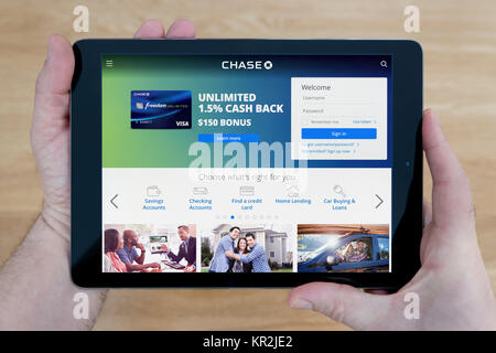 A man looks at the Chase Bank website on his iPad tablet device, shot against a wooden table top background (Editorial - Stock Photo