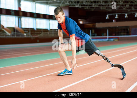 Handicapped Runner Stretching in Stadium - Stock Photo
