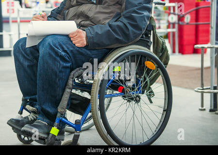No face disabled, handicapped person on wheeled chair fills the form blank or makes a shopping list in the market - Stock Photo