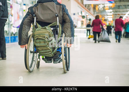 No face aged disabled, handicapped person on wheeled chair among people without disabilities in the mall of market - Stock Photo