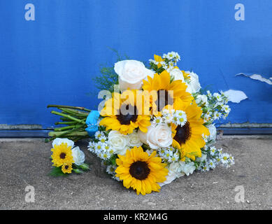 Photo of a bridal bouquet and boutonniere of bright yellow sunflowers with white hydrangea, roses and Monte Casino - Stock Photo