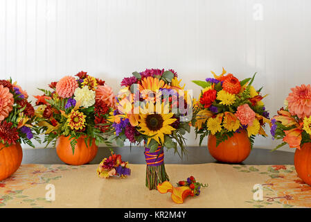 Photo of fall wedding flowers. The sunflower bridal bouquet is surrounded by centerpieces of fresh flowers in real - Stock Photo