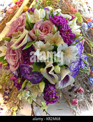 Photo of a colorful nosegay bridal bouquet stuffed with purple calla lilies, rose Lisianthus, pink roses, alstroemeria, - Stock Photo