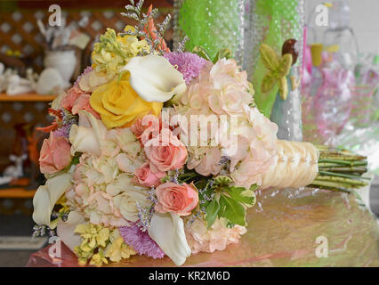 Photo of a bridal bouquet with yellow roses, calla lilies, lavender asters, coral roses, peach hydrangea, yellow - Stock Photo