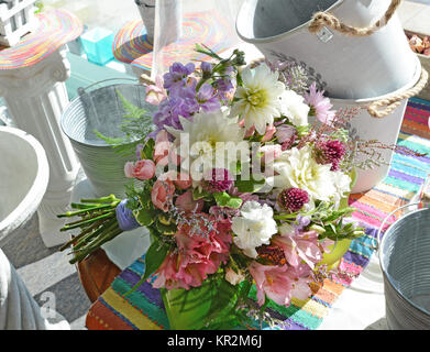 Photo of a colorful summer bridal bouquet overflowing with garden flowers like dahlias, stock, allium, roses alstroemeria - Stock Photo