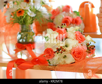 Photo of a vivid orange, peach and white wedding bouquet. Calla lilies, roses, hypericum berries and hydrangea look - Stock Photo