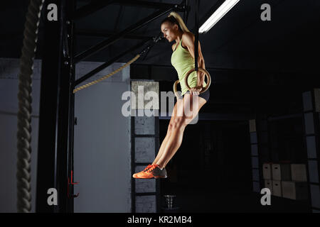 Low angle shot of a sportswoman doing ring dips at the crossfit gym. Gorgeous young woman performing crossfit workout - Stock Photo