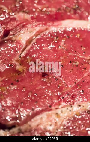 raw new york steaks on cutting board seasoned - Stock Photo