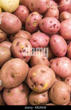 red potatoes from market shelves real with flaws and bruises - Stock Photo