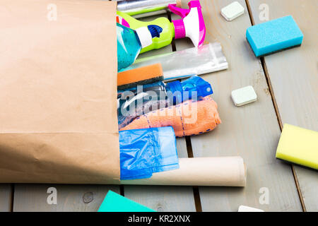 Full paper bag of different house cleaning product on wooden table - Stock Photo