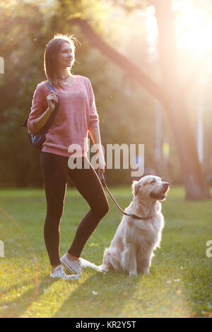 Image of beautiful woman on walk with dog in summer park - Stock Photo
