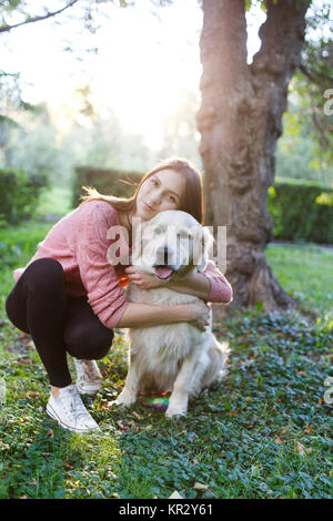Photo of girl hugging dog on lawn - Stock Photo