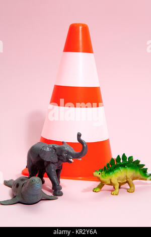 a collection animals beside a traffic cone on a vibrant pink background. Minimal still life photography - Stock Photo