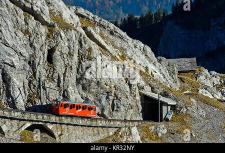 Red railcar of the Pilatus Railway in a steep passage in the Pilatus massif, Alpnachstad near Lucerne, Switzerland - Stock Photo